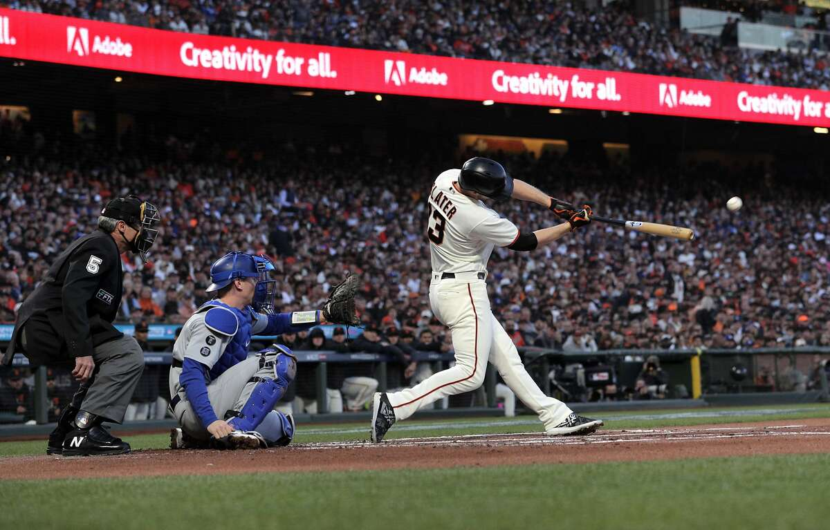Austin Slater (13) hits a double in the first inning as the San Francisco Giants played the Los Angeles Dodgers in Game 2 of the National League Division Series at Oracle Park in San Francisco, Calif., on Saturday, October 9, 2021.