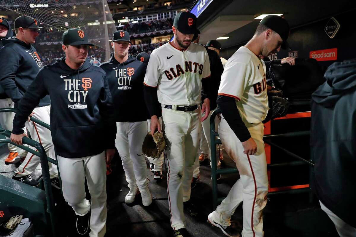 Buster Posey and Kris Bryant leave the dugout after the Giants' loss to the Dodgers in Game 2 of the National League Division Series. Game 3 will be played in Los Angeles.