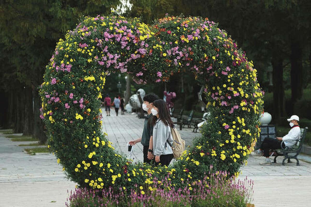 A couple passes by a heart-shaped chrysanthemum flower arrangement.