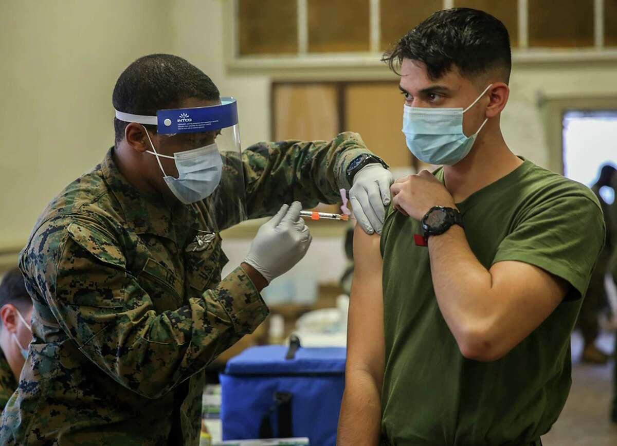 Military medical personnel at Camp Lejeune, N.C., administer coronavirus vaccines in January.