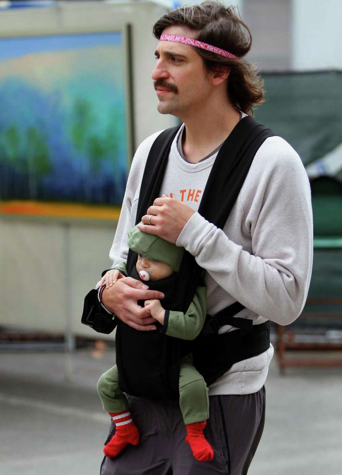 Stephen Puschel, of Cos Cob, carries his three-month-old son Baz as they attend Bruce Museum's 40th annual outdoor Art Festival held on the museum grounds in Greenwich, Conn., on Saturday October 9, 2021. The festival features original work by artists and craftspeople from around the country. All artists attend in person, and all works are for sale. The hours are 10 a.m. to 5 p.m. on Sunday. Tickets are available at BruceMuseum.org.
