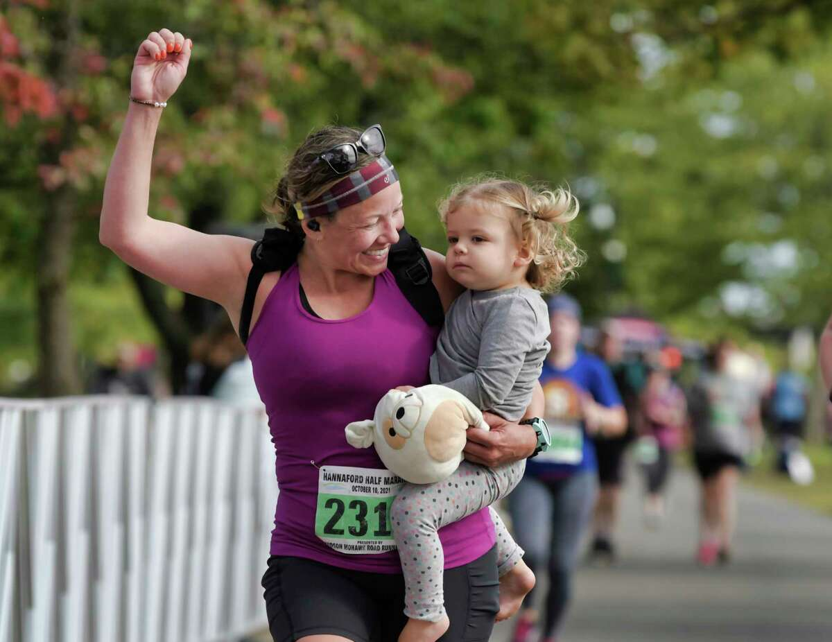 Jennifer Galeo of Mechanicville carries her daughter, Emerson Taylor, 2, the final yards of the Hannaford Half Marathon on Sunday, Oct. 10, 2021, in Albany, N.Y. The Mohawk Hudson River Marathon & Hannaford Half Marathon took place on Sunday for the first time in two years.