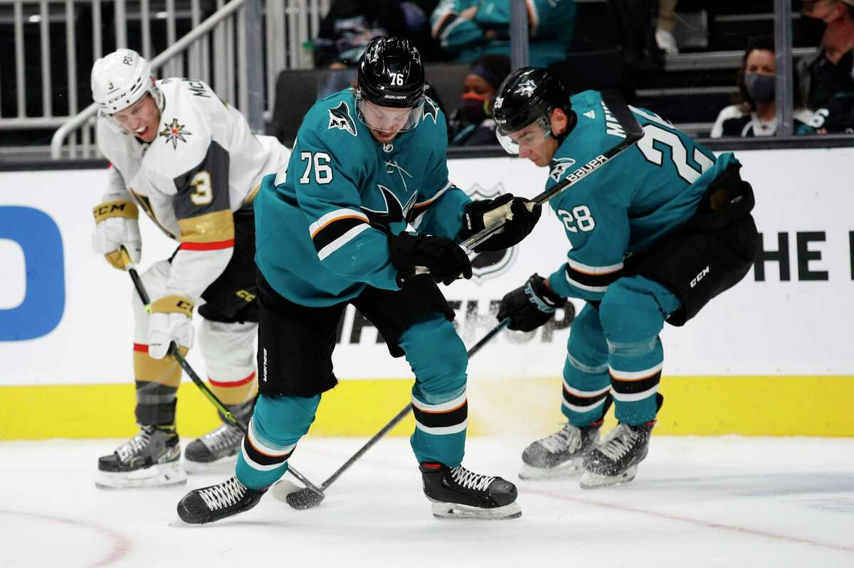 Vegas Golden Knights defenseman Brayden McNabb (3) battles for the puck against San Jose Sharks Jonathan Dahlen (76), and right wing Timo Meier (28) in the first period of a preseason NHL hockey game in San Jose, Calif., Saturday, Oct. 9, 2021. (AP Photo/Josie Lepe)