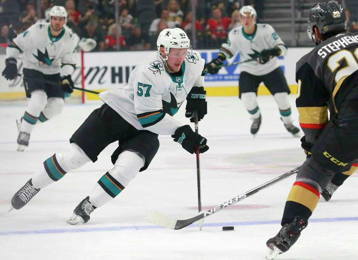 San Diego Sharks' Adam Raska (57) controls the puck near Vegas Golden Knights center Chandler Stephenson (20) in the first period of an NHL hockey preseason game Sunday, Sept. 26, 2021, in Las Vegas. The Sharks won 4-2. (AP Photo/Ronda Churchill)