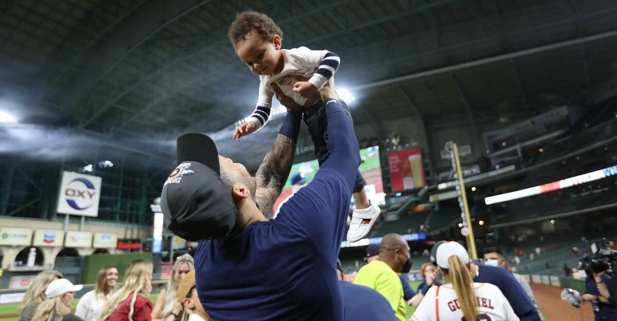 Houston Astros shortstop Carlos Correa (1) holds Aiden Maldonado, one of Martin Maldonado's children after Houston clinched the AL West with their 3-2 win over Tampa Bay Rays after an MLB baseball game at Minute Maid Park, Thursday, September 30, 2021, in Houston.
