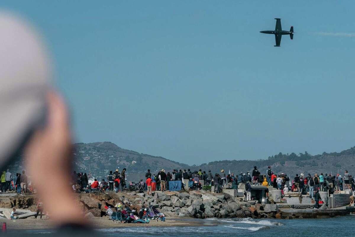 A plane flies over San Francisco as people watch the Fleet Week Air Show in San Francisco.