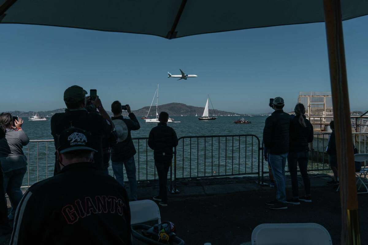 People watch a United Airlines Boeing 777 fly in low over the bay, from inside the Flight Deck tent at the Fleet Week Air Show in San Francisco.