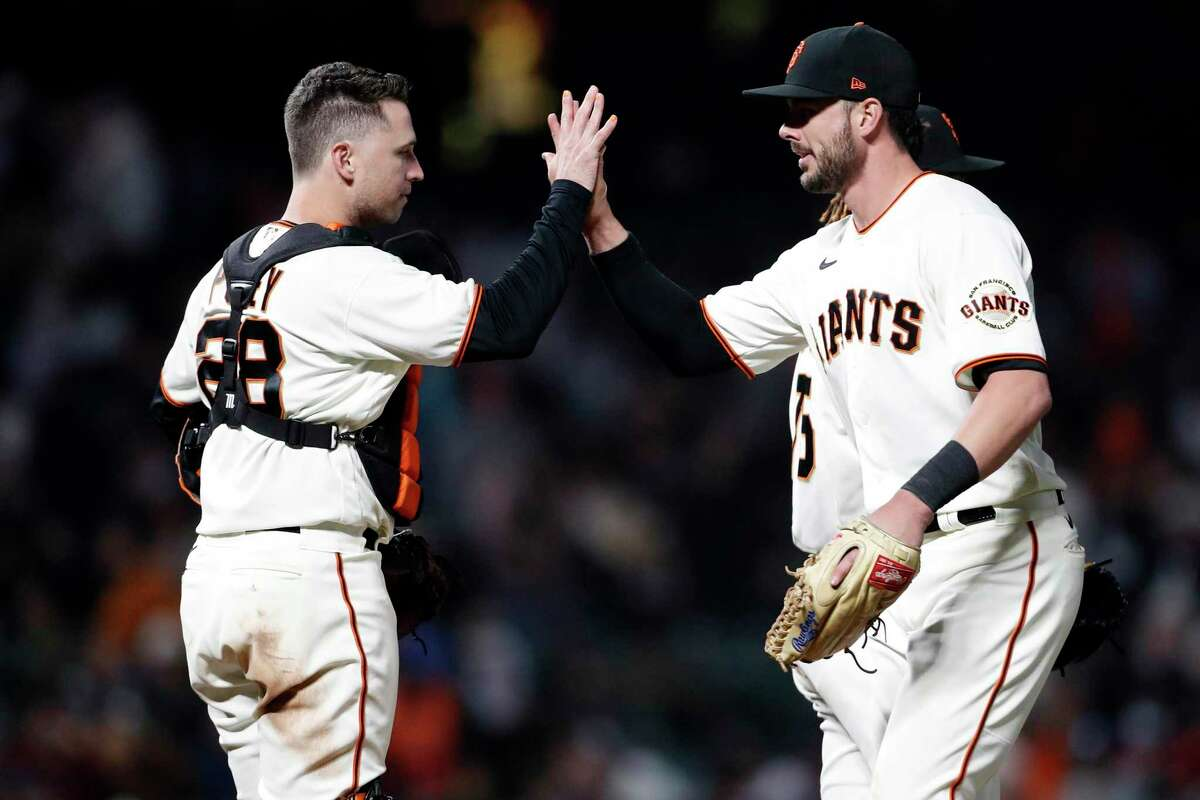 San Francisco Giants' Kris Bryant and Buster Posey high five after Giants' 1-0 win over Arizona Diamondbacks during MLB game at Oracle Park in San Francisco, Calif., on Tuesday, September 29, 2021.