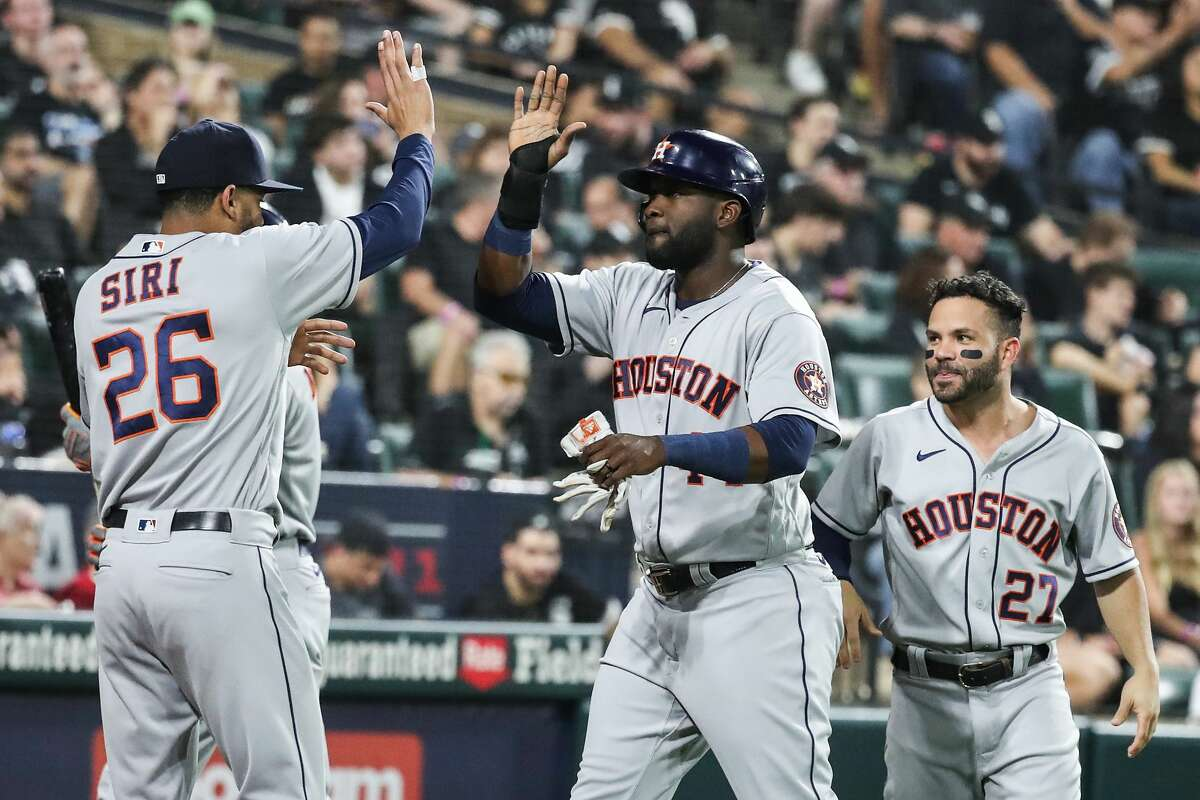 Houston Astros designated hitter Yordan Alvarez (44) high fives with Jose Siri (26) after Alvarez scored on a 2-run double by Kyle Tucker during the second inning against the Chicago White Sox in Game 3 of the American League Division Series Sunday, Oct. 10, 2021, in Chicago.