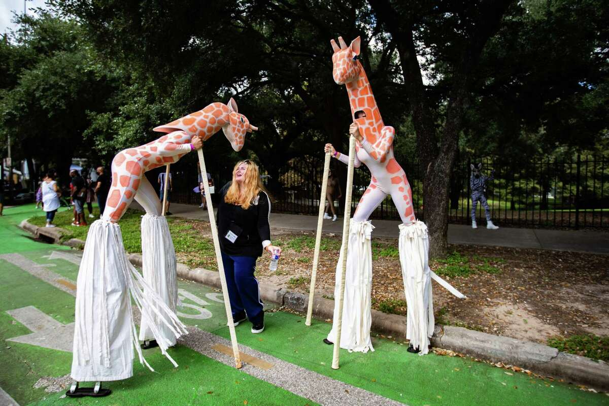 Sonia Guimbellot interacts playfully with Carver Aldine Dance Company dancers dressed as giraffes at the Bayou City Art Festival by the Sam Houston Park, Sunday, Oct. 10, 2021, in Houston.