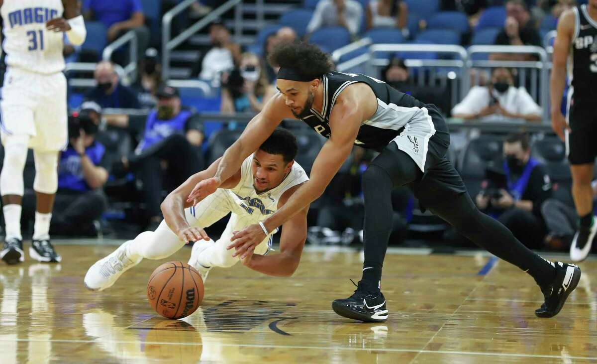 Orlando Magic guard Jalen Suggs, left, dives for the ball in front of the Spurs' Derrick White during the first half of a preseason game, Sunday, Oct. 10, 2021, in Orlando, Fla.
