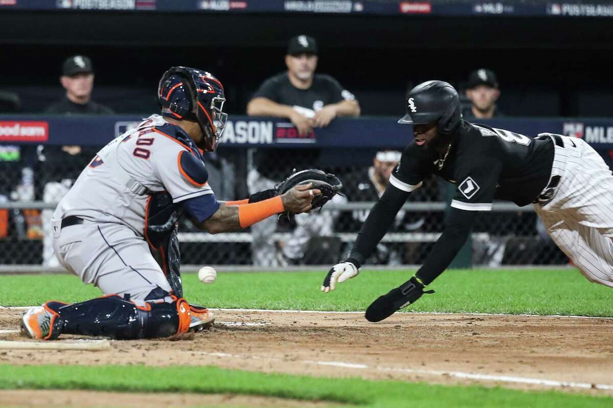 The ball gets past Houston Astros catcher Martin Maldonado (15) as Chicago White Sox center fielder Luis Robert (88) slides to score on a throwing error by first baseman Yuli Gurriel during the fourth inning in Game 3 of the American League Division Series Sunday, Oct. 10, 2021, in Chicago.