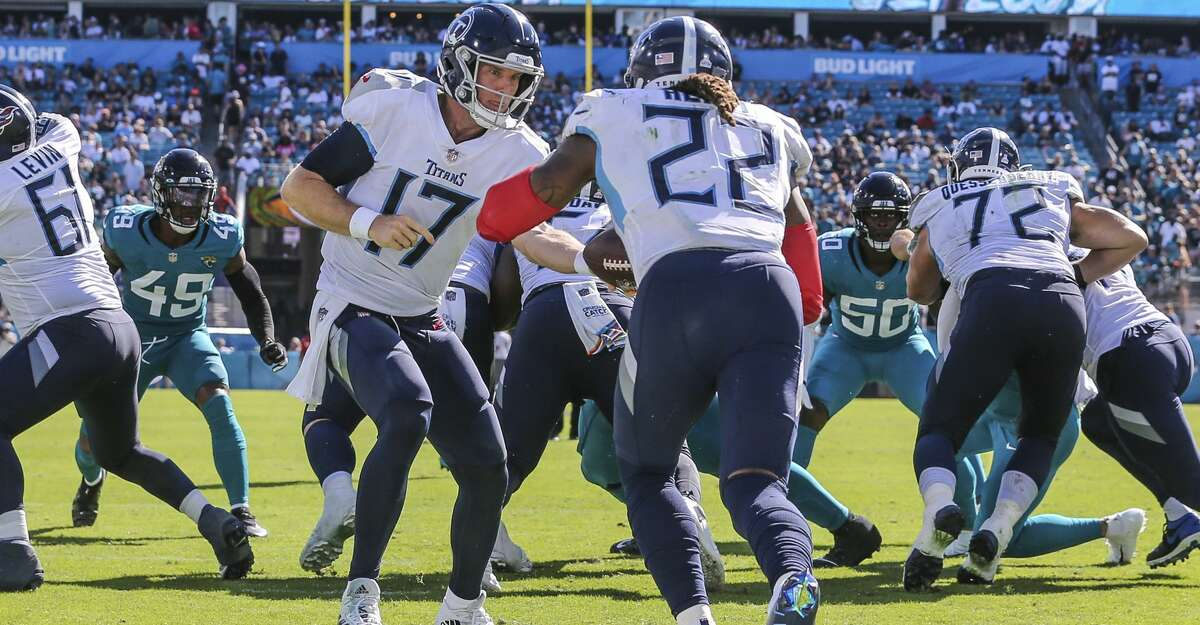 Tennessee Titans quarterback Ryan Tannehill (17) hands off the ball to running back Derrick Henry (22) during an NFL football game against the Jacksonville Jaguars, Sunday, Oct. 10, 2021, in Jacksonville, Fla. The Titans defeated the Jaguars 37-19. (AP Photo/Gary McCullough)