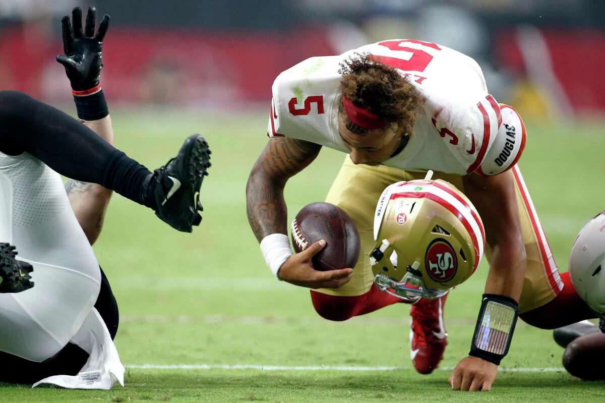 San Francisco 49ers quarterback Trey Lance (5) loses hit helmet on a hit against the Arizona Cardinals during the second half of an NFL football game, Sunday, Oct. 10, 2021, in Glendale, Ariz. (AP Photo/Ralph Freso)