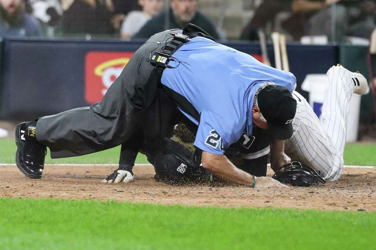 Umpire Tom Hallion takes a tumble as Chicago's Luis Robert storms to the plate in the fourth inning to put the White Sox up 8-6. Robert scored after a throw home from Astros first baseman Yuli Gurriel hit Yasmani Grandal, who was running on the infield grass toward first, and got past catcher Martin Maldonado.
