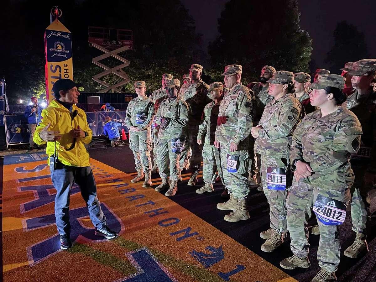 Boston Marathon Race Director Dave McGillivray, left, talks to member of the Massachusetts National Guard before the start the 125th running of the Boston Marathon in Hopkinton, Mass., early Monday, Oct. 11, 2021.