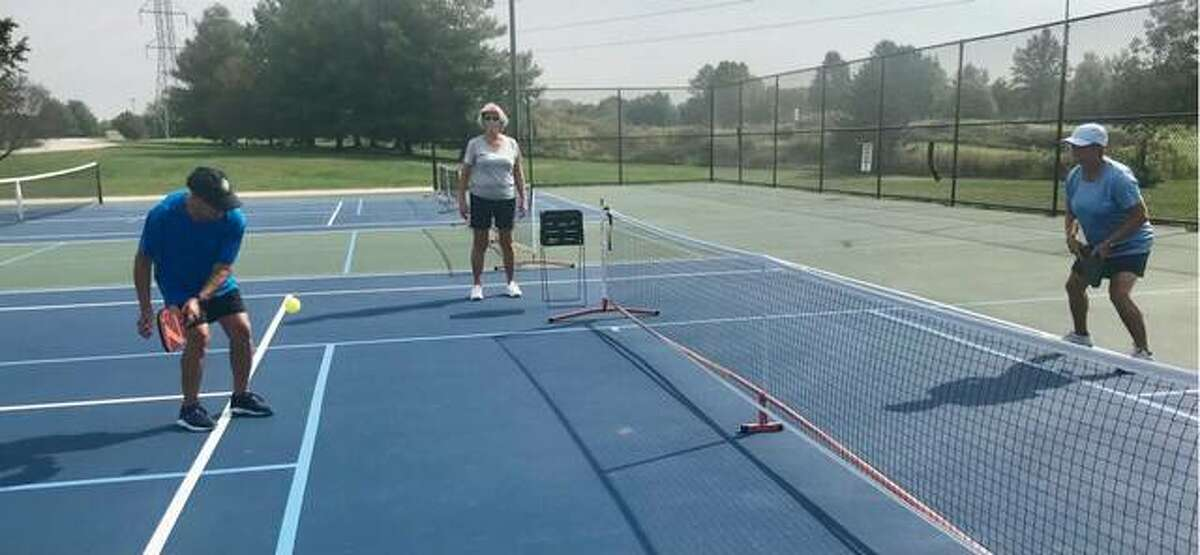 Alan Lipe, left, returns a dink shot to Tracie Steckel during the dinking competition Saturday at Gordon Moore Park in observance of World Pickleball Day.