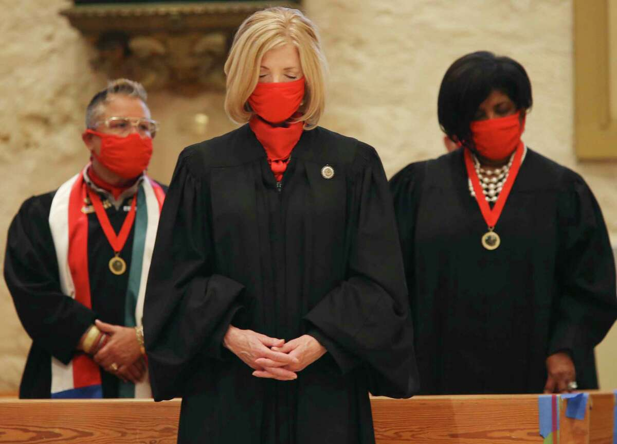 Fourth Court of Appeals Chief Justice Sandee Marion bows her head in prayer during the Red Mass at San Fernando Cathedral on Oct. 22, 2020. Named the Red Mass because of the scarlet robes worn by judges and the red vestments worn by priests in honor of the Holy Spirit, it is held each year to bless and guide the administration of justice. Behind her are Bexar County Judge County Court 13 Judge Rosie Speedlin Gonzalez, left, and County Court 12 Judge Yolanda Huff.