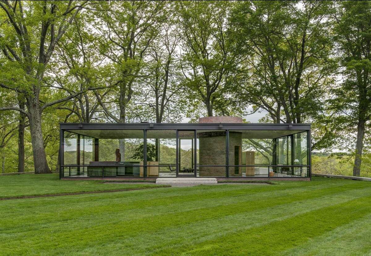 The Glass House in New Canaan, completed in 1949 by renowned Mid-century architect Philip Johnson, is a rectangular, symmetrical one-story building, primarily enclosed with steel-framed glass with a brick cylinder structure for a fireplace and bathroom.