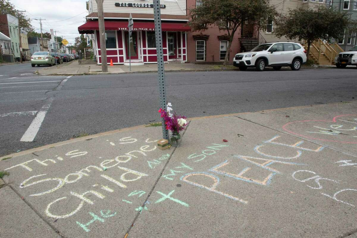 """Messages are written in chalk on the sidewalk at the scene of Saturday night's mass shooting that killed Alexander Bolton and wounded six people on Monday, Oct, 11, 2021 in Albany, N.Y. Bolton's father, Jeff, wrote the words """"Alex he is my son"""" underneath one of the messages. The shooting happened at the Lounge located at 117 North Lake Ave."""