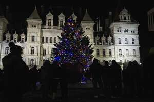 People gather around the tree to take photos at the Empire State Plaza during the New York State holiday tree lighting ceremony on Sunday, Dec. 8, 2019, in Albany, N.Y. (Paul Buckowski/Times Union)