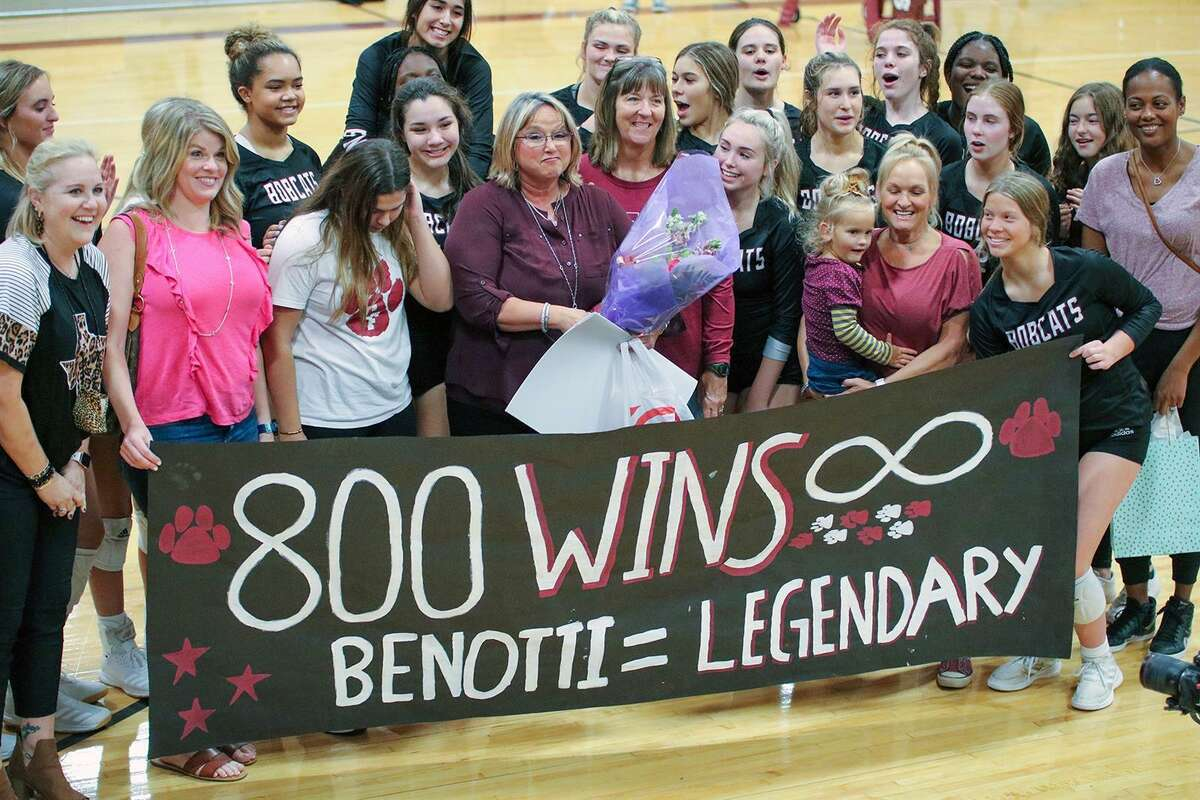 Cy-Fair High School volleyball coach Donna Benotti, holding flowers, is surrounded by current and former volleyball team members after the long-time coach picked up her 800th career victory. The Bobcats beat Springs Woods on Oct. 1 for the milestone win.