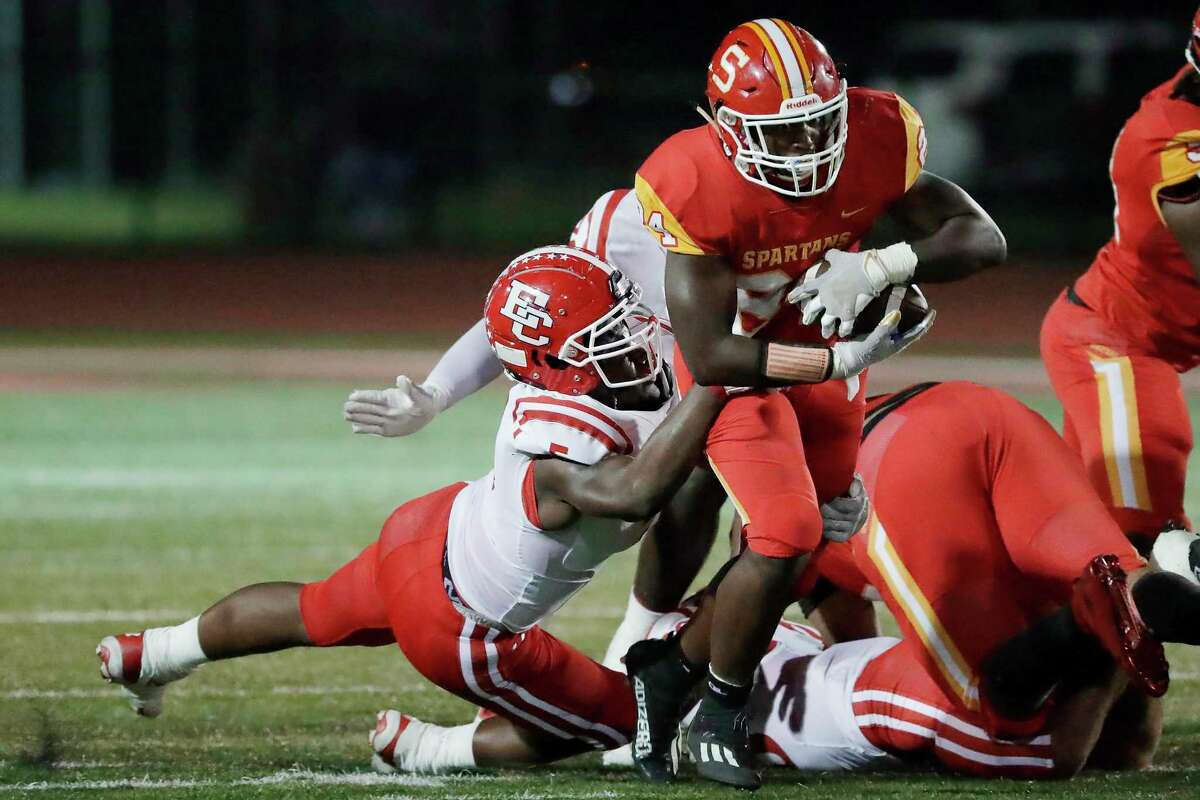 Stafford running back Jamaal Wiley, right, slips through the tackle attempt by El Campo defensive lineman Clarence Farrow, left, during the first half of a high school football game Friday, Oct. 8, 2021 in Houston, TX.