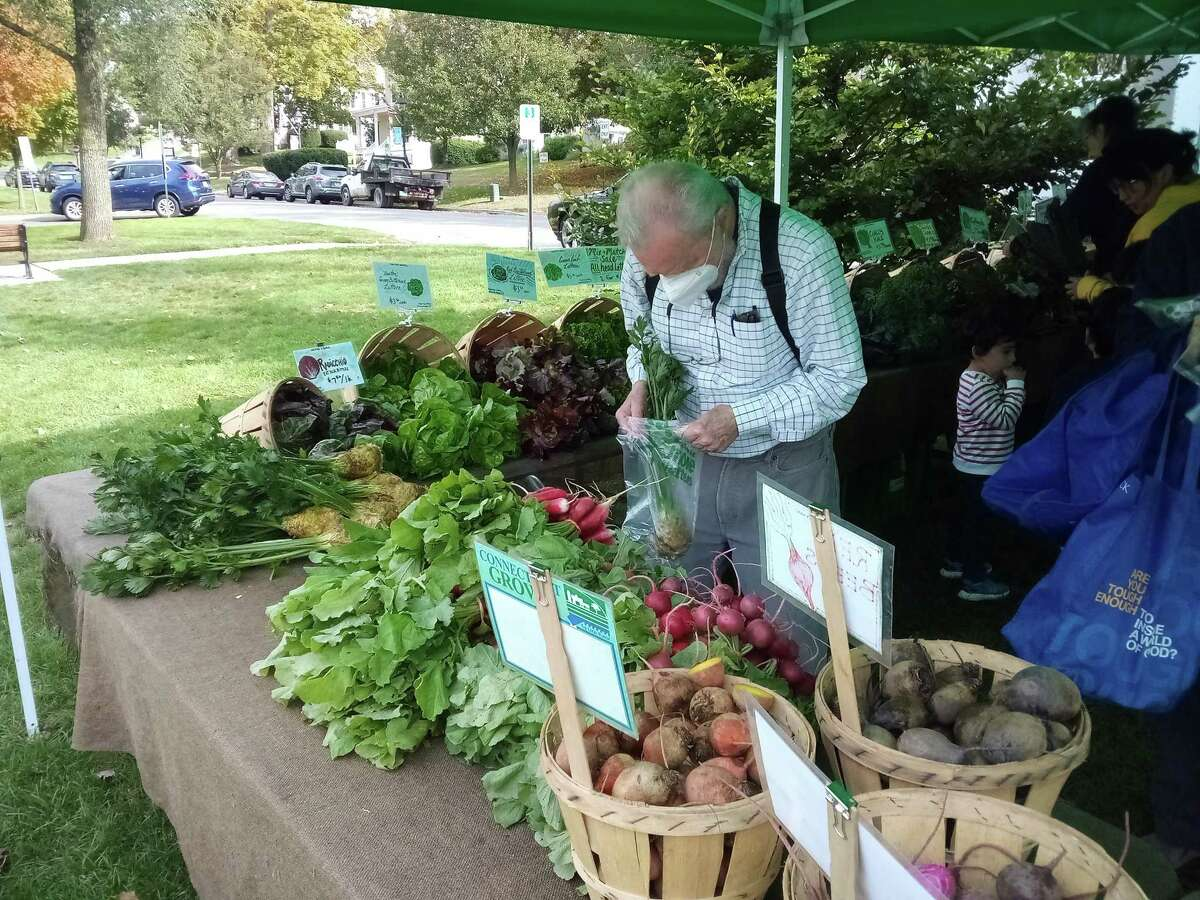 New Milford's weekly farmers market is held on the green every Saturday from 9 a.m. to noon. New Milford resident Jeff Campbell fills a bag from the Fort Hill Farm stand.