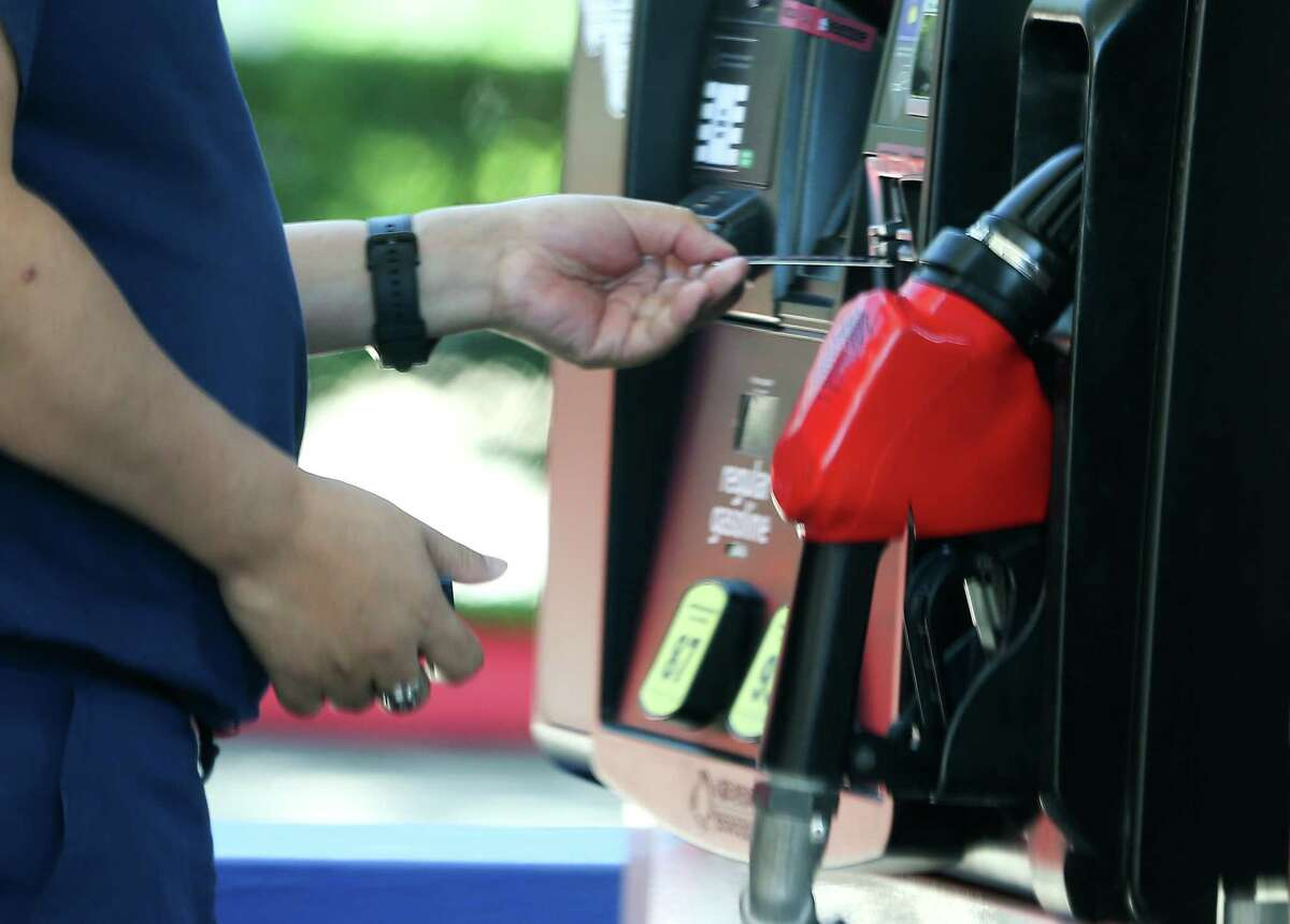 A person pays for gasoline in Houston on Monday, Oct. 11, 2021. Oil prices jump over $80 a barrel for the first time since 2014.