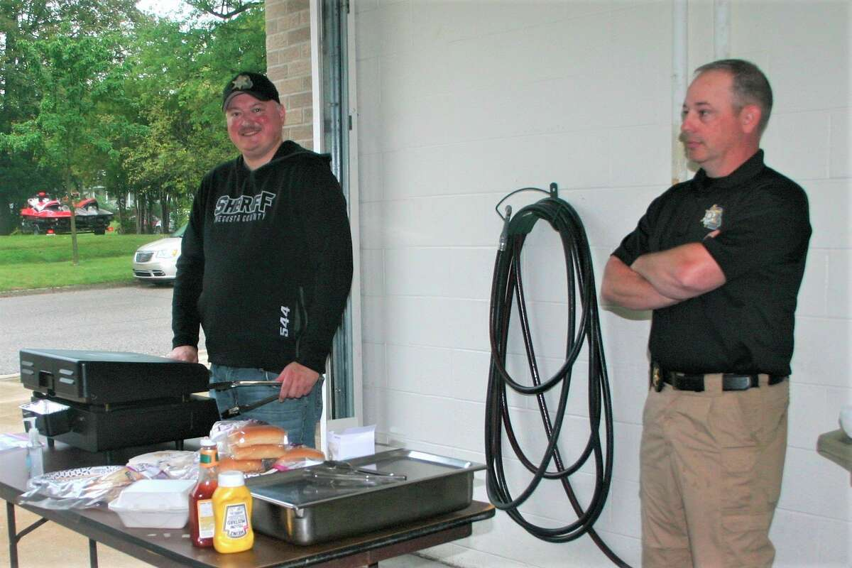 Lieutenant Mark Danielson grills up the hot dogs as Undersheriff Mike Williams looks on during the employee appreciation lunch Friday. (Pioneer photo/Cathie Crew)