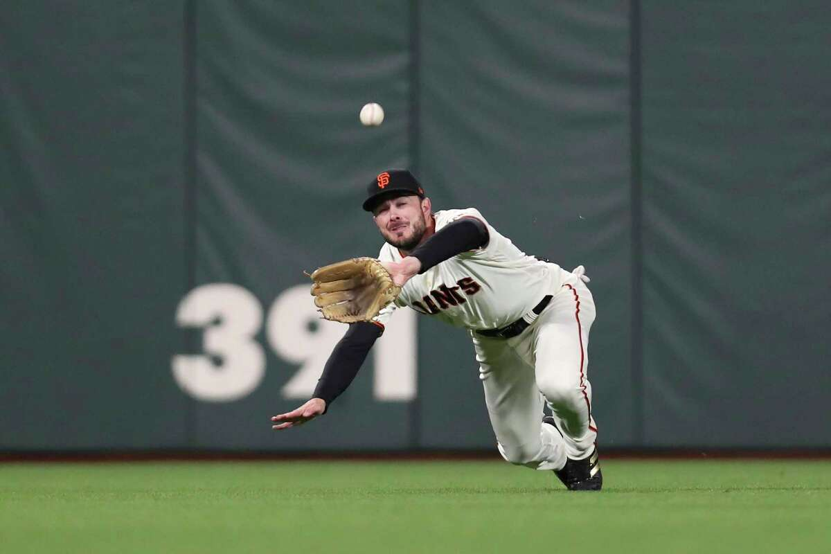 San Francisco Giants center fielder Kris Bryant catches a fly out hit by Los Angeles Dodgers' Trea Turner during the seventh inning of Game 2 of a baseball National League Division Series Saturday, Oct. 9, 2021, in San Francisco. (AP Photo/Jed Jacobsohn)
