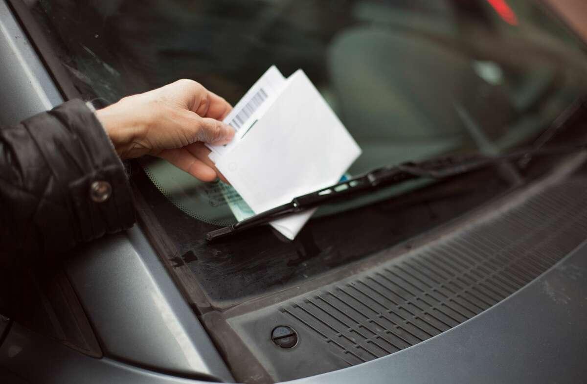 A parking ticket under awindshield wiper.