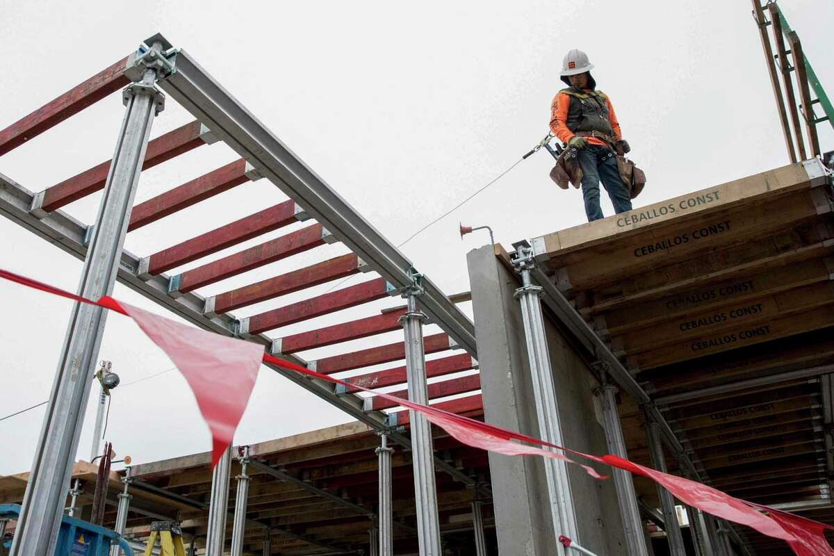 Workers construct the Aquatic Shattuck apartments in 2020 at Shattuck Avenue and Carleton Street in Berkeley, a city long resistant to new housing.