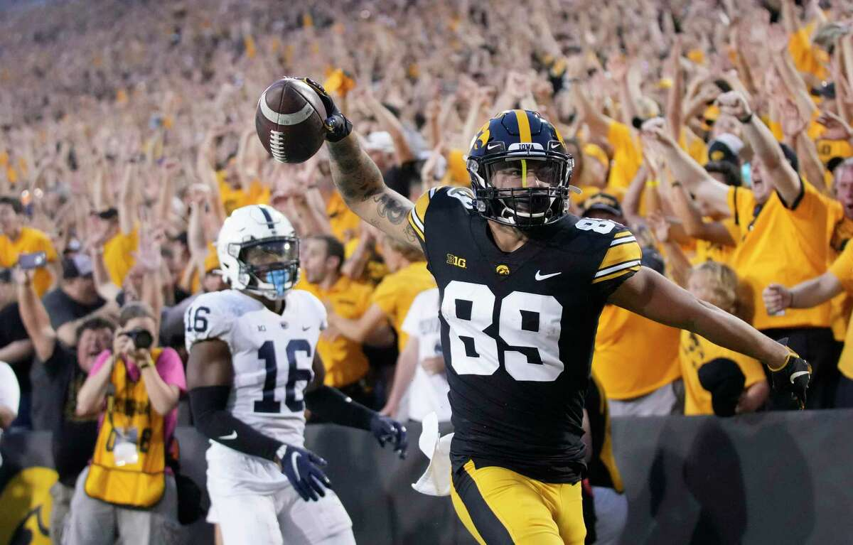 Iowa wide receiver Nico Ragaini (89) reacts after scoring a touchdown in front of Penn State safety Ji'Ayir Brown during the second half Saturday.