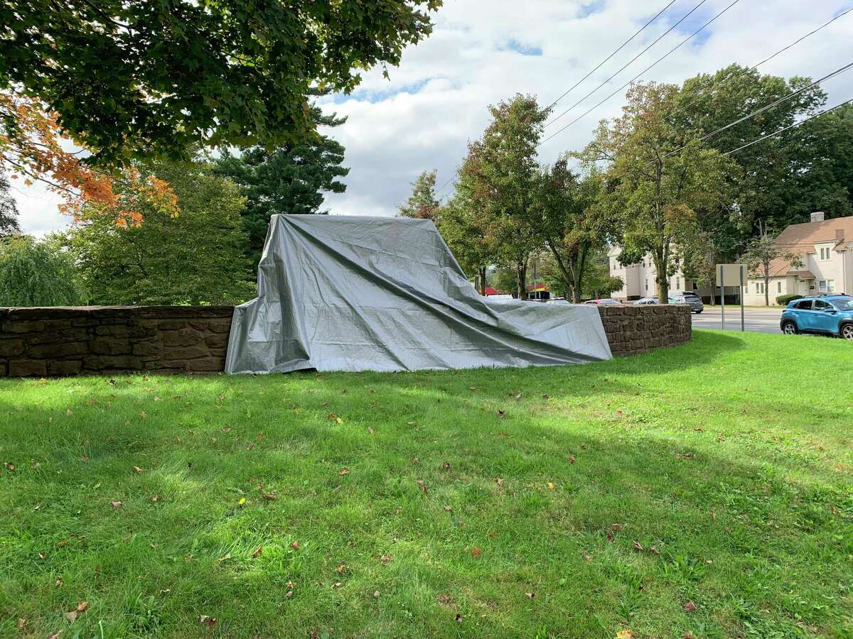 The sign and the brownstone wall of the Indian Hill Cemetery are covered after being vandalized with spraypaint overnight.