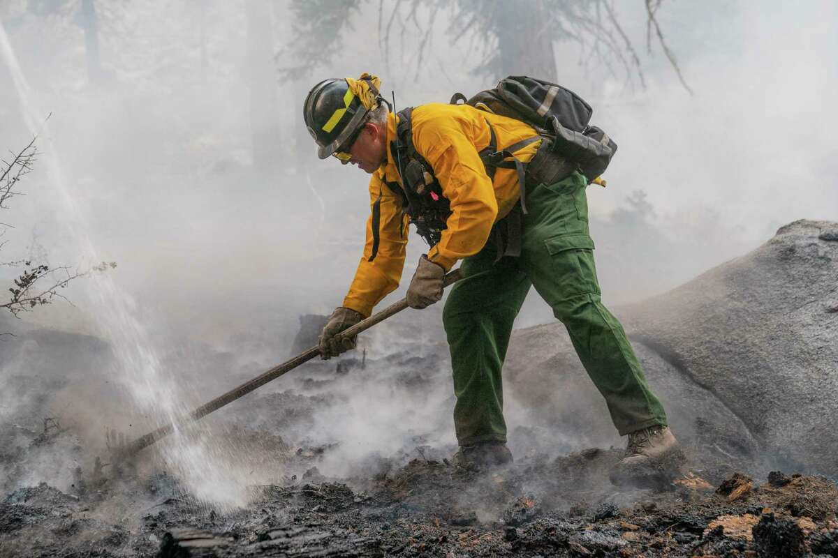 Engine Boss Mark Peffer of the Bothell Fire Department in Washington works alongside his crew after knocking down a flare up at the Caldor Fire along South Upper Truckee Road near South Lake Tahoe, Calif., on Wednesday, September 1, 2021.