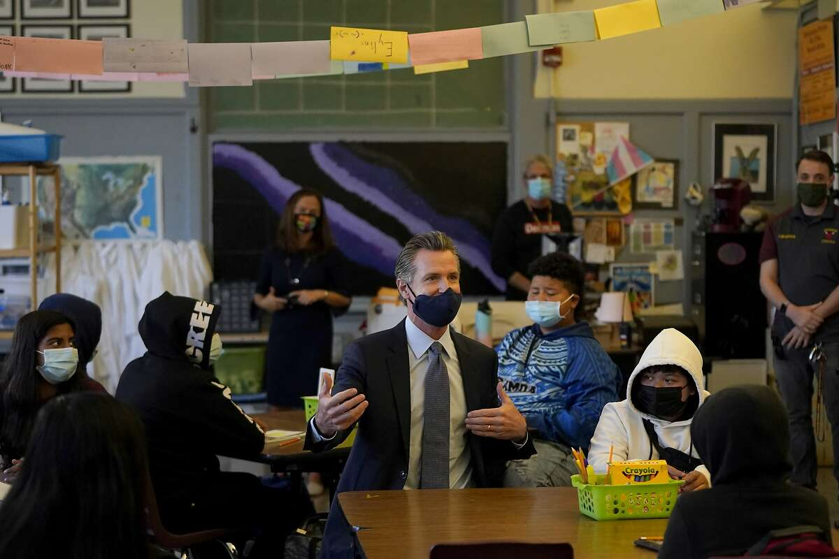 FILE - In this Oct. 1, 2021 file photo Gov. Gavin Newsom, middle, speaks to students in a seventh grade science class at James Denman Middle School in San Francisco. California schools have a few statewide requirements for how schools apply COVID rules for schools but leave most details up to the local districts, leading to a dizzying patchwork of approaches that parents and teachers say can be confusing and frustrating. (AP Photo/Jeff Chiu, File)