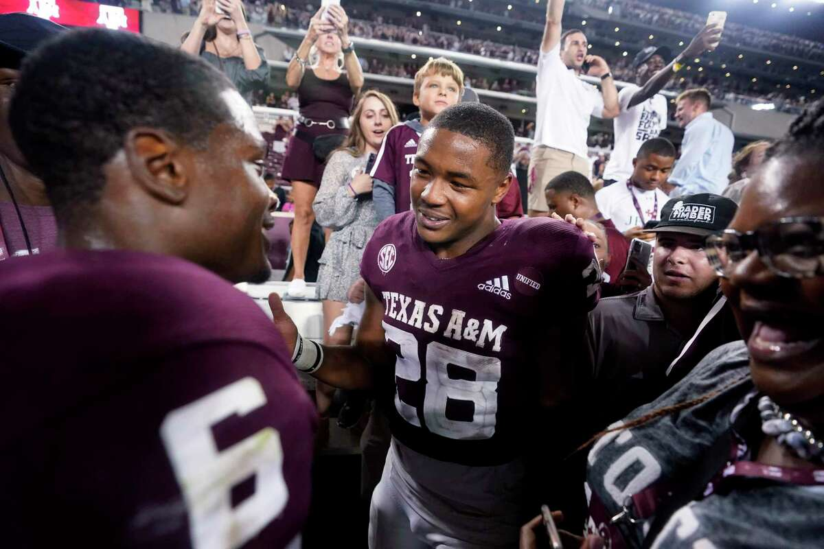 Texas A&M running backs Isaiah Spiller (28) and Devon Achane (6) smile after the team's win over Alabama during on Saturday, Oct. 9, 2021, in College Station.