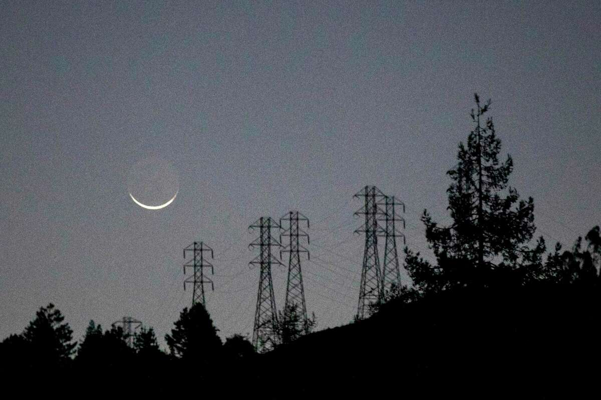 The moon sets over a darkened hillside and PG&E high voltage power lines in Oakland.