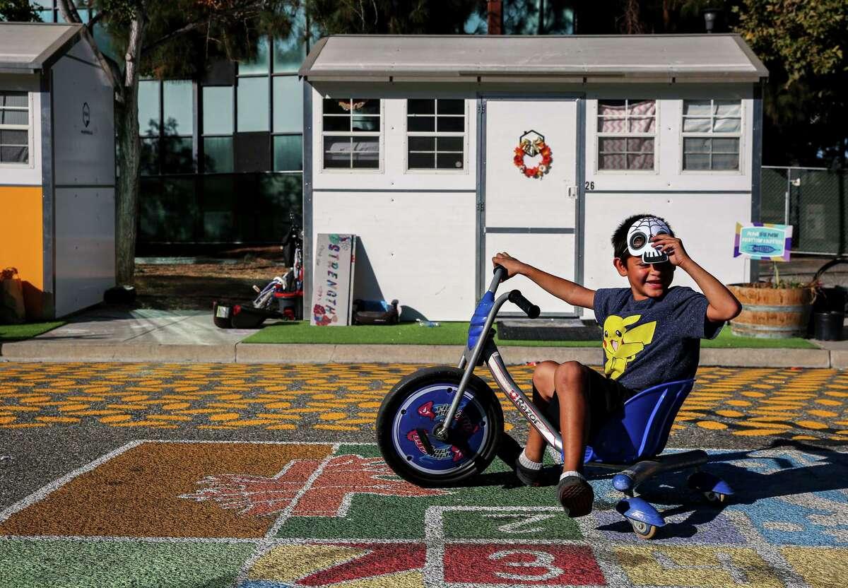 Samuel Diaz, 7, rides his bike near his family's tiny home at Casitas de Esperanza shelter in San Jose.