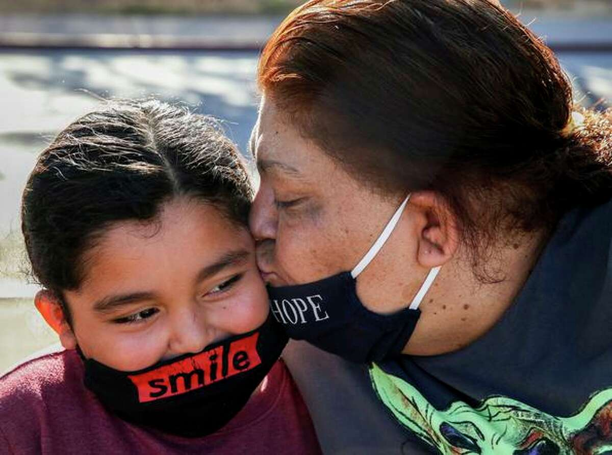 Maria Castañeda kisses her son Jesus Benitaz-Castañeda, 6, on the cheek while waiting for the train in San Jose. Castañeda and her three children have been living at a tiny home village in the city for seven months after moving from shelter to shelter and overcrowded homes. The family is participating in a Santa Clara County effort to house all homeless families by 2025.