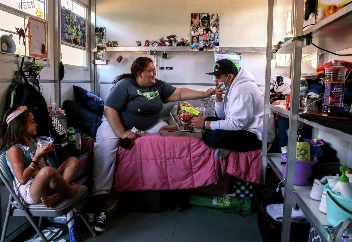 Maria Castañeda, left, sits in her tiny home with her 15-year-old son Angel Odilon, right, and neighbor Ximena Diaz, 6, while at Casitas de Esperanza shelter in San Jose, Calif., on Sunday, Oct. 10, 2021. Currently, there are about 538 homeless families in Santa Clara County, where officials hope that one-time pandemic funding and rethinking of housing vouchers will help house homeless families by 2025.