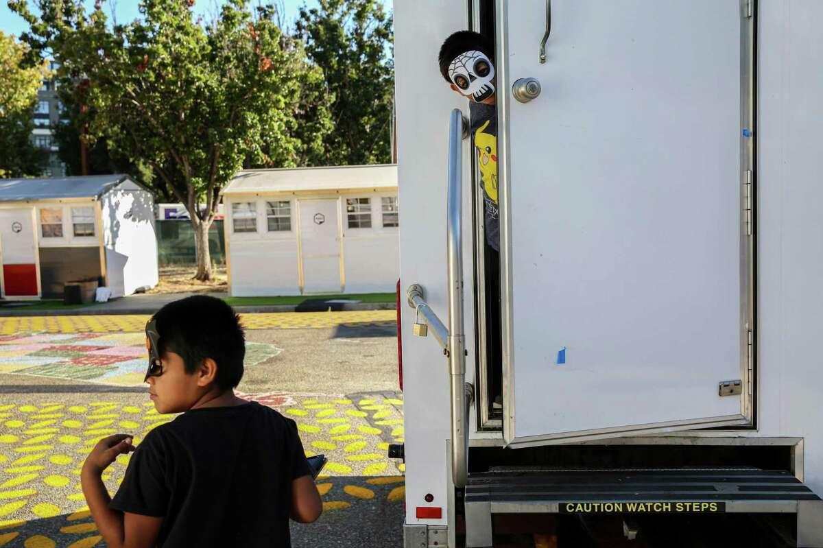 Samuel Diaz, 7, looks out of a community bathroom at Casitas de Esperanza shelter in San Jose, Calif. on Sunday, Oct. 10, 2021.