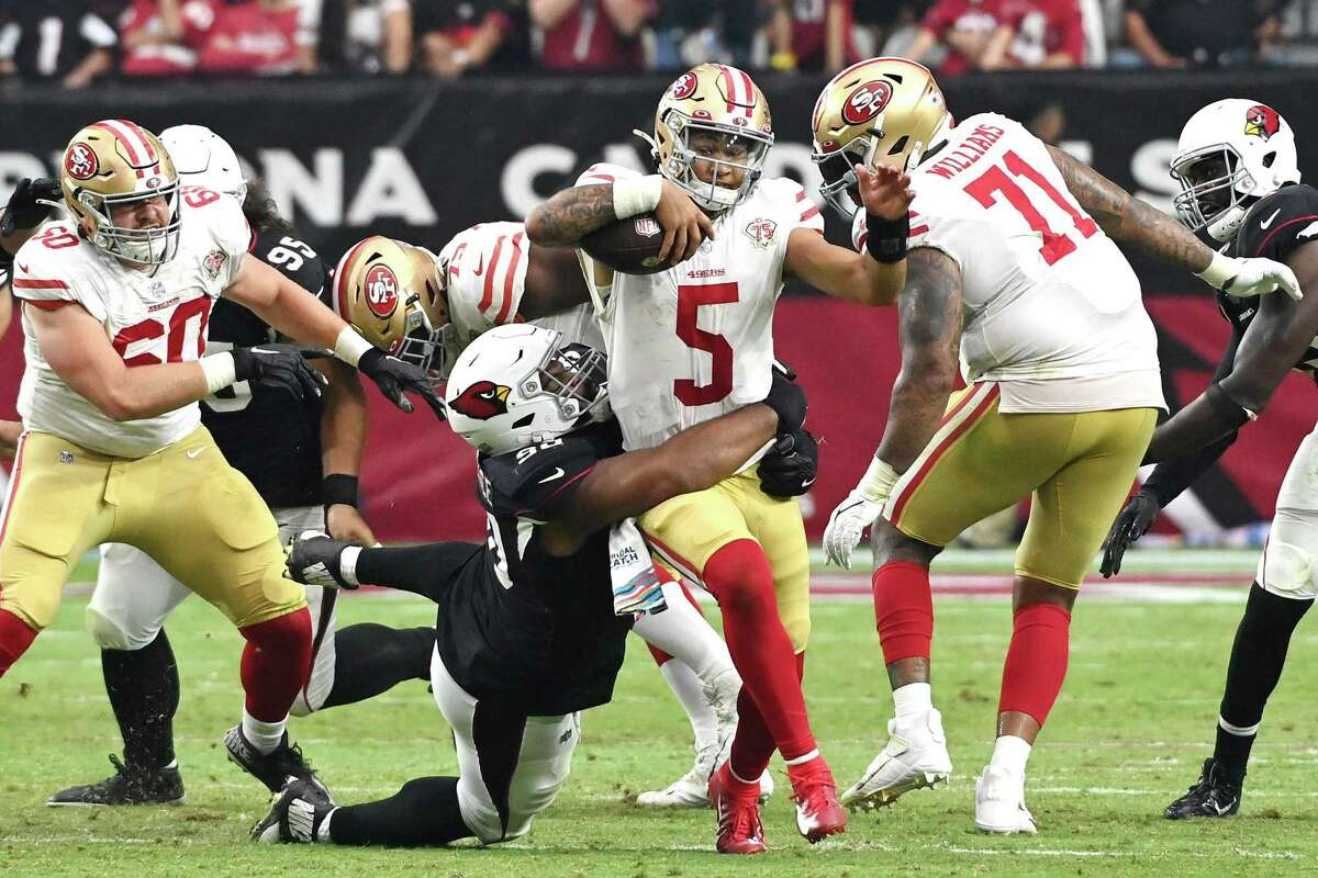 GLENDALE, ARIZONA - OCTOBER 10: Trey Lance #5 of the San Francisco 49ers is tackled by Rashard Lawrence #90 of the Arizona Cardinals during the fourth quarter at State Farm Stadium on October 10, 2021 in Glendale, Arizona. (Photo by Norm Hall/Getty Images)