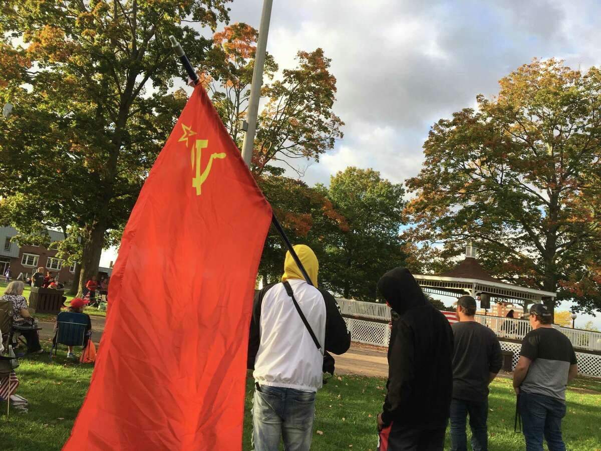 Two young men, one of whom, Dean Bravo, was carrying a Soviet-era hammer-and-sickle flag, showed up and surprised some people at the East Haven Columbus Day Trump Rally on the East Haven Green on Monday, Oct. 11, 2021.