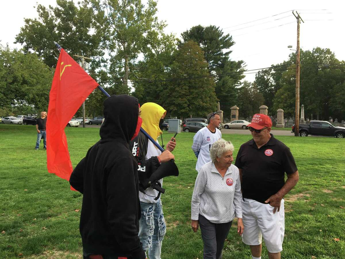 East Haven Republican Town Council candidate Donna Richo and East Haven Columbus Day Trump Rally organizer Peter Cianelli talk with two young men, one of whom, Dean Bravo, was carrying a Soviet-era hammer-and-sickle flag at the rally on the East Haven Green on Monday, Oct. 11, 2021.