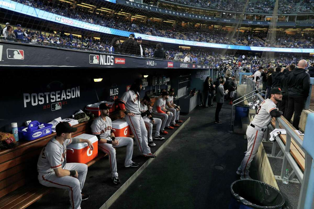 The San Francisco Giants sit in their dugout before the starting Game 3 of the National League Division Series versus the Los Angeles Dodgers at Dodger Stadium in Los Angeles, Calif. on Monday, Oct. 11, 2021.