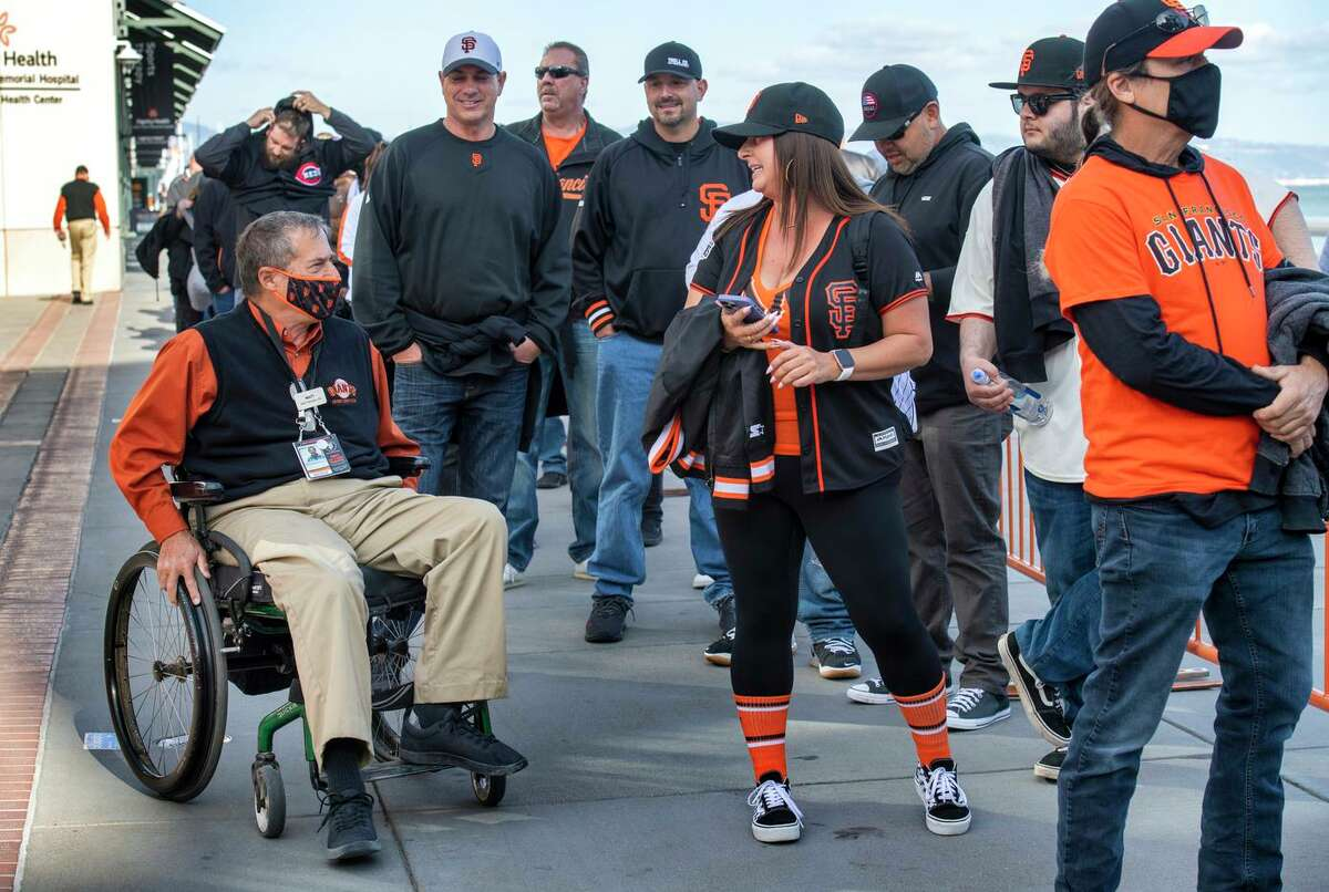Matthew Farruggio helps fans navigate Oracle Park's Lefty O'Doul gate before Game 1 of the National League Division Series between the Giants and Dodgers.