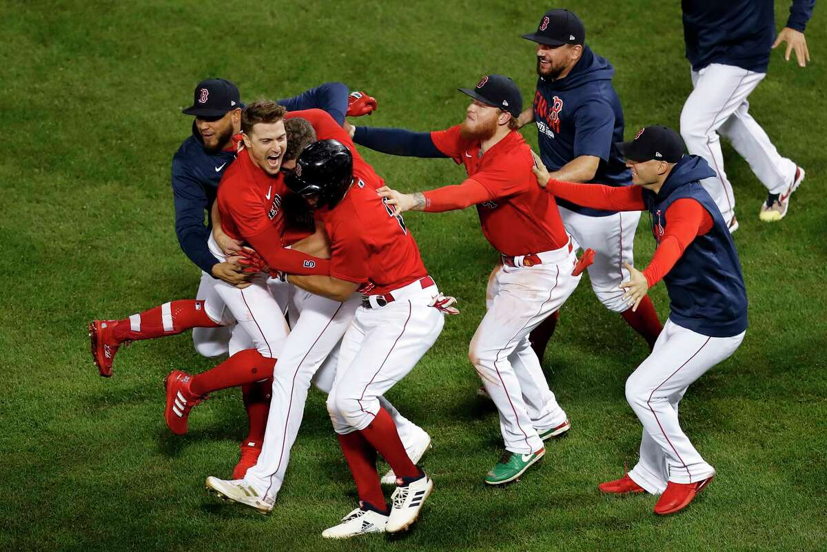 The Boston Red Sox celebrate after beating the Tampa Bay Rays on a sacrifice fly ball by Enrique Hernandez (5) during the ninth inning during Game 4 of a baseball American League Division Series, Monday, Oct. 11, 2021, in Boston. The Red Sox won 6-5.