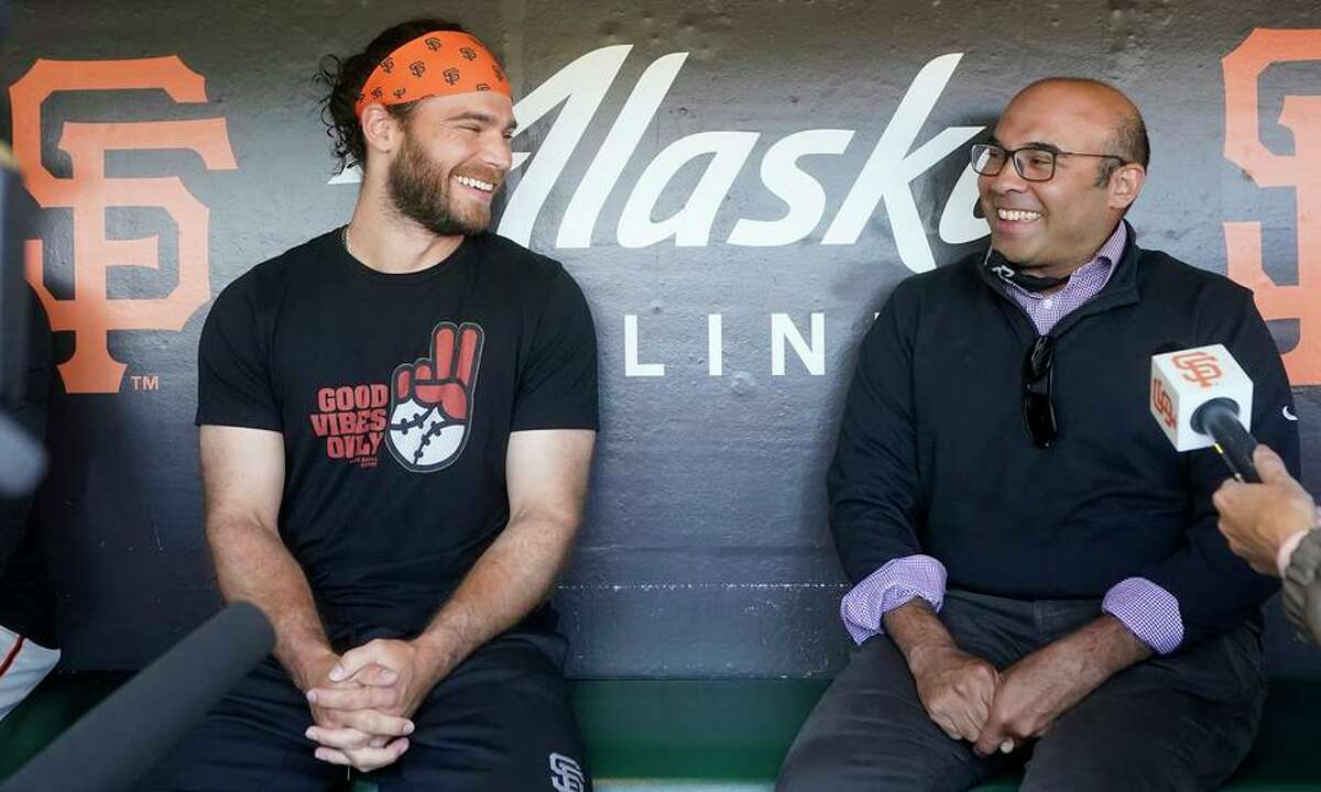 San Francisco Giants shortstop Brandon Crawford, left, smiles next to the team's president of baseball operations, Farhan Zaidi, while speaking with reporters before a baseball game between the Giants and the Colorado Rockies in San Francisco, Friday, Aug. 13, 2021. Crawford is being rewarded for one of his best seasons yet, agreeing to a new two-year contract that takes him through the 2023 season. (AP Photo/Jeff Chiu)
